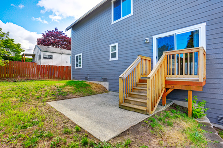 Fenced backyard with small concrete patio area and stairs. Large grey house exterior. Northwest, USA