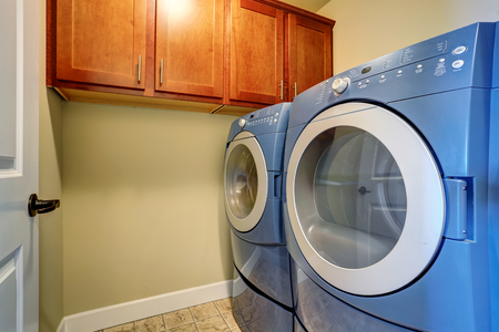 cabinets: Laundry interior with modern blue appliances and cabinets. Stock Photo