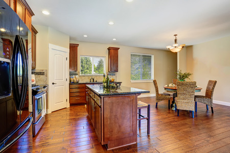 black appliances: Luxury kitchen room with modern black appliances. Kitchen is connected with dining area. Furnished with dinner table and nice wicker chairs. Northwest, USA Stock Photo