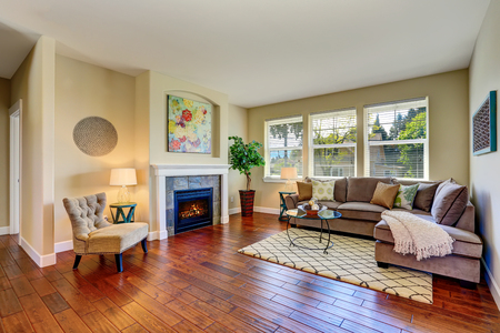 hardwood floor: Cozy living room interior with fireplace, beige walls and hardwood floor. Northwest, USA