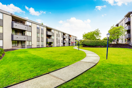 Large beige apartment building with three floors and balconies. Well kept lawn. Northwest, USA. Standard-Bild