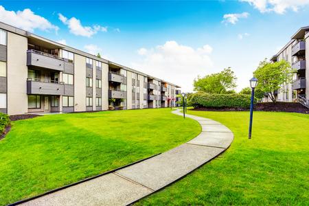 Groot beige flatgebouw met drie vloeren en balkons. Goed onderhouden gazon. Northwest, VS.