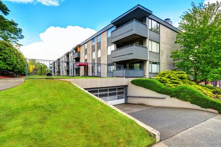 Gran edificio de apartamentos beige con tres plantas y balcones. Césped bien cuidado. Noroeste, Estados Unidos.