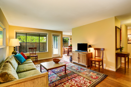 traditional living room: Traditional living room interior with green sofa, hardwood floor and rug. Northwest, USA