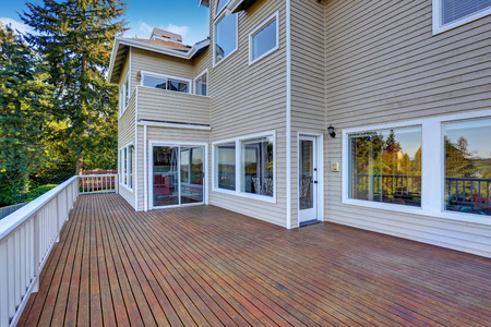 deck: Two story house with wooden walkout deck overlooking backyard garden. Northwest, USA Stock Photo