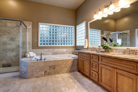 Luxury bathroom interior with vanity with granite counter top, large mirror and tile floor. Northwest, USA