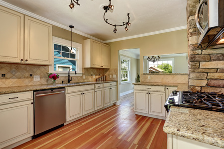 Kitchen room interior with white cabinets, stainless steel and hardwood floor. Northwest, USA