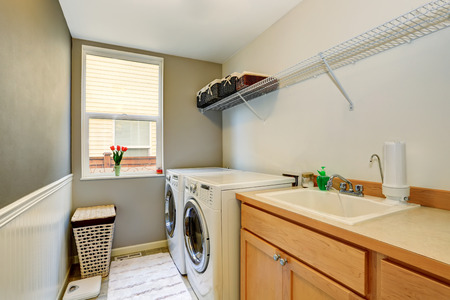 cabinets: Laundry room with wood cabinets and tile floor. Northwest, USA