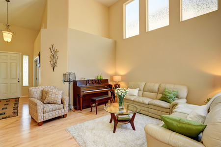 Cozy living room interior in light tones with leather sofas and nice curtains. Also antique piano. Northwest, USA