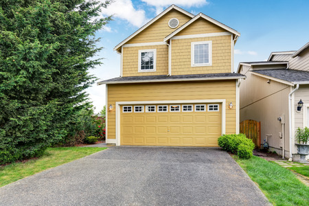 two level house: Curb appeal. Yellow two level house exterior with garage. Northwest, USA