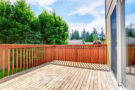 garden styles: One story house with wooden walkout deck overlooking backyard garden. Northwest, USA
