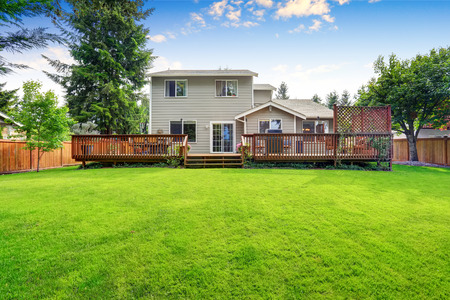 Back yard house exterior with spacious wooden deck with patio area and attached pergola. Northwest, USA