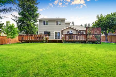 Volver patio de la casa exterior con amplia terraza de madera con zona de patio y pérgola adjunto. Noroeste, EE.UU.
