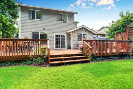 Achtertuin huis buitenkant met ruime houten dek met een patio en een aangrenzende pergola. Northwest, USA Stockfoto