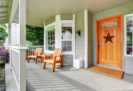 white trim: Spacious concrete floor porch with wooden chairs and nice entry door. Northwest, USA