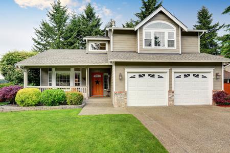Curb beroep. Amerikaans huis buitenkant met dubbele garage, betonnen vloer veranda en goed onderhouden gazon. Northwest, USA