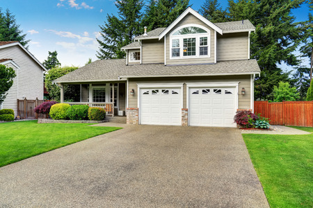 Curb appeal. American house exterior with double garage, concrete floor porch and well kept lawn. Northwest, USA