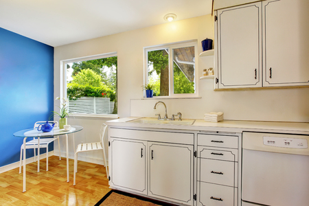 cabinets: Small kitchen room interior with white cabinets, blue walls and glass dining table. Northwest, USA