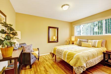 Bedroom interior in yellow tones with hardwood floor. Northwest, USA