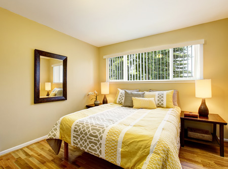 northwest: Bedroom interior in yellow tones with hardwood floor. Northwest, USA