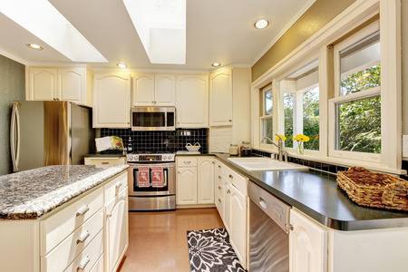kitchen island: White kitchen room with granite tops. Kitchen island and tile floor. Northwest, USA Stock Photo
