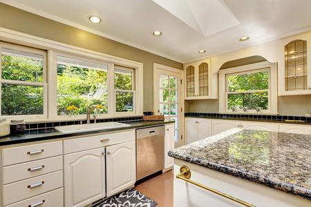 white kitchen: White kitchen room with granite tops. Kitchen island and tile floor. Northwest, USA Stock Photo