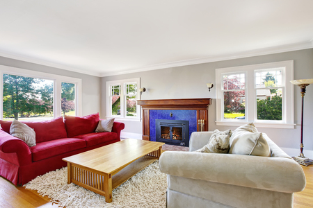 interior decor: Cozy living room interior with red and beige sofas and blue tile fireplace. Northwest, USA