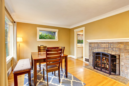 Cozy dining area with wooden table set, hardwood floor and fireplace. Northwest, USA