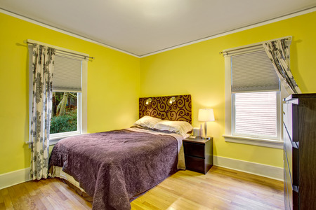 yellow walls: Bedroom interior with yellow walls, deep brown furniture and hardwood floor. Northwest, USA