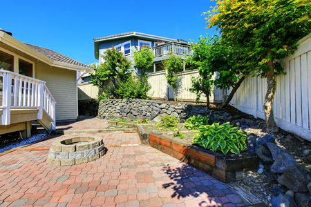 northwest: Fenced backyard with rocks desing and concrete tile walkway. Northwest, USA Stock Photo