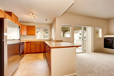 Empty kitchen room interior with wooden cabinets and tile floor. Northwest, USA
