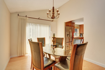 dining table and chairs: Dining room interior with table set. Glass table and leather chairs. Northwest, USA