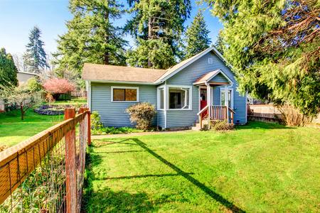 Kleine grijze huis met houten dek. Voortuin met bloembed en gazon. Northwest, USA