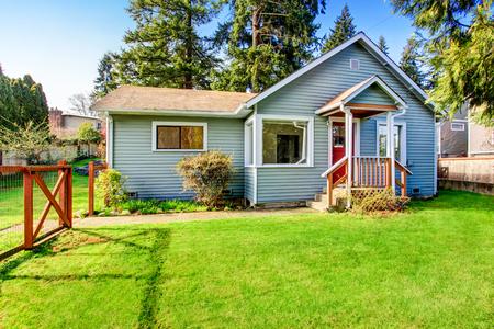 Pequeña casa gris con cubierta de madera. Patio delantero con cama de flores y el césped. Noroeste, EE.UU.