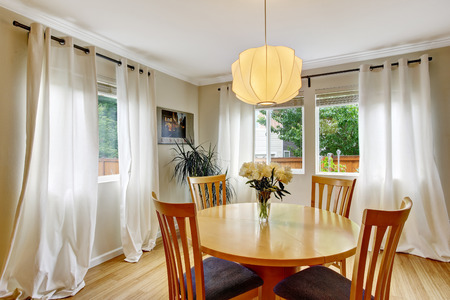 Cozy dining area with table set and curtains in creme tones. Northwest, USA