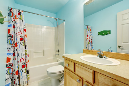 Kids bathroom interior in blue tones with wooden cabinets and colorful shower curtain. Northwest, USA