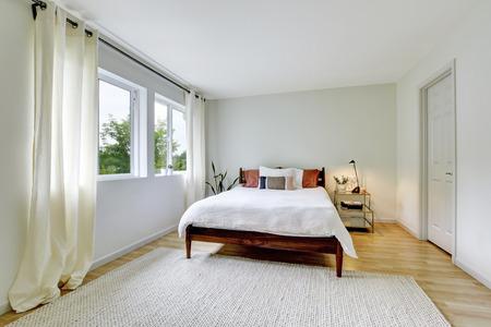 Bedroom interior in light tones with wooden bed and hardwood floor. Northwest, USA Stock Photo