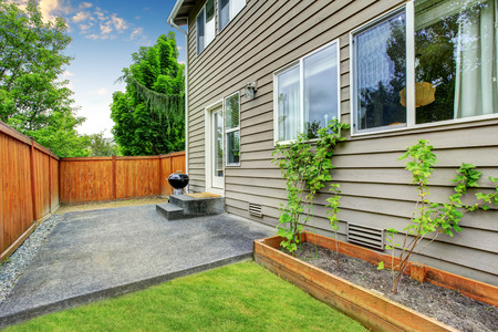 lawn area: Fenced backyard concrete floor patio area and well kept lawn. Northwest, USA Stock Photo