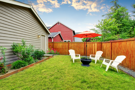 fenced: Fenced backyard patio area with opened red umbrella and well kept lawn. Northwest, USA
