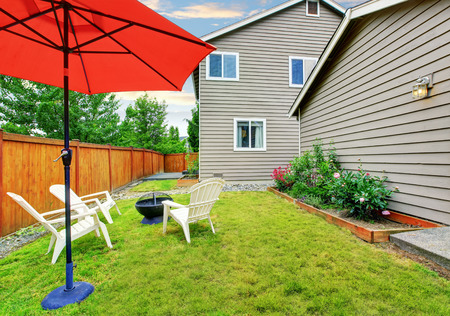 lawn area: Fenced backyard patio area with opened red umbrella and well kept lawn. Northwest, USA