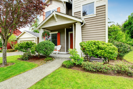 House exterior with siding trim, red entry door and concrete walkway. Northwest, USA 版權商用圖片
