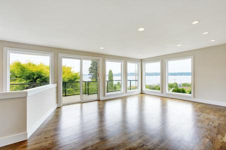 hardwood floor: Empty living room interior in light tones with hardwood floor. Northwest, USA