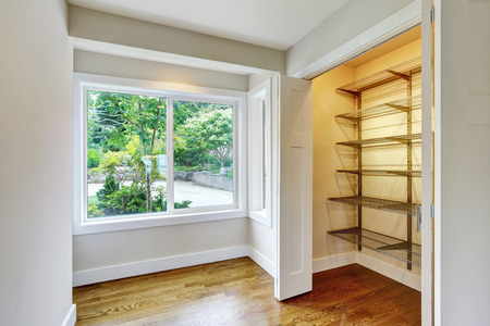 Hallway interior with hardwood floor and opened doors to walk-in closet with shelves. Northwest, USA