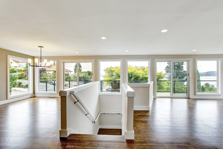 Open floor plan. Ligth tone room interior with hardwood floor. View of stairs to first floor. Northwest, USA Archivio Fotografico
