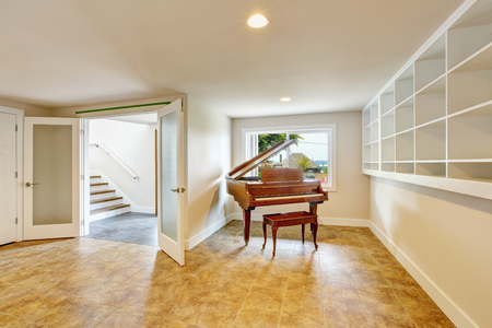 Open floor plan interior with light tones walls and tile floor. Also buil-in shelves. Antique piano. Northwest, USA Stock Photo