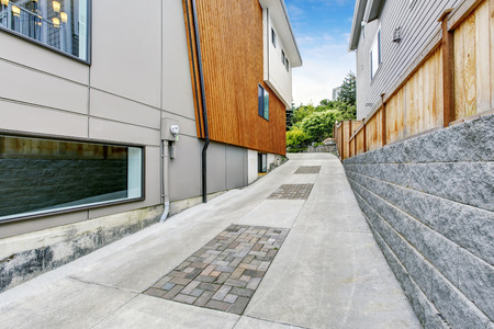 Luxury driveway to garage near modern house with wooden pannel trim. Concrete driveway. Northwest, USA