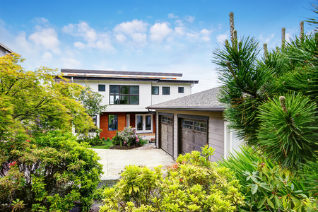 northwest: Luxury two level house exterior  with separate double garage and concrete driveway. View from garden. Northwest, USA Stock Photo