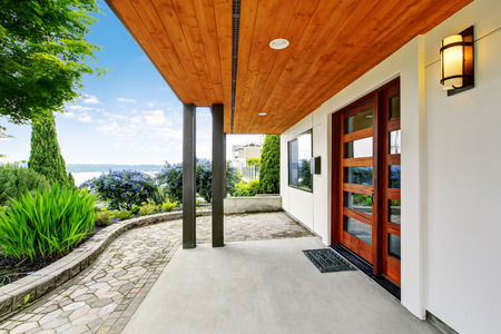 entryway: Modern house entryway with concrete walkway and amazing water view. Northwest, USA