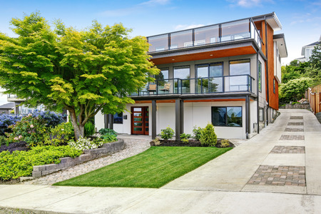 Modern three level house exterior with wooden trim and spacious two balconies areas. Northwest, USA
