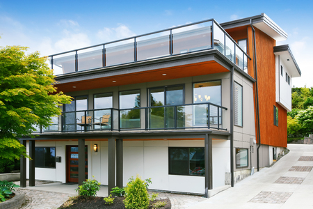 house exterior: Modern three level house exterior with wooden trim and spacious two balconies areas. Northwest, USA
